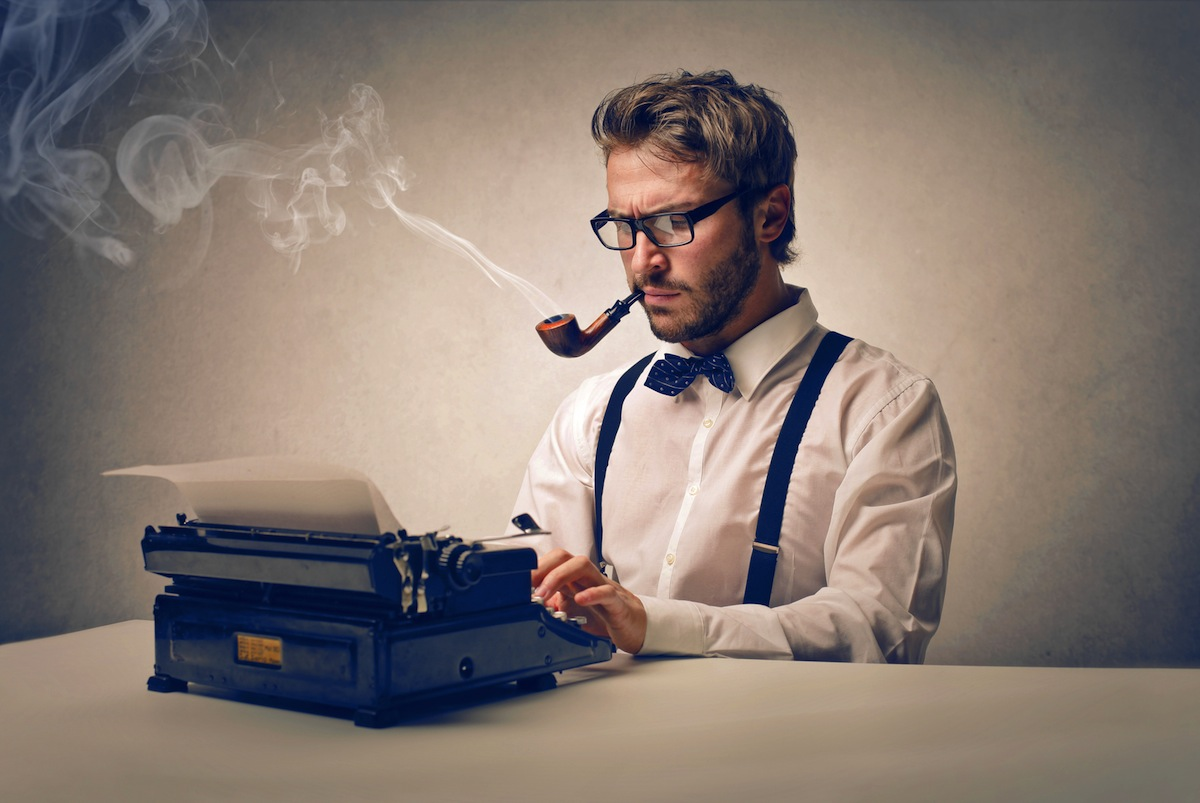 Picture of a man using a writing machine and smoking with a pipe